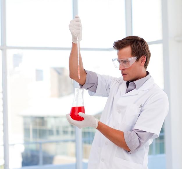 Jovem cientista examina um tubo de ensaio Foto Premium