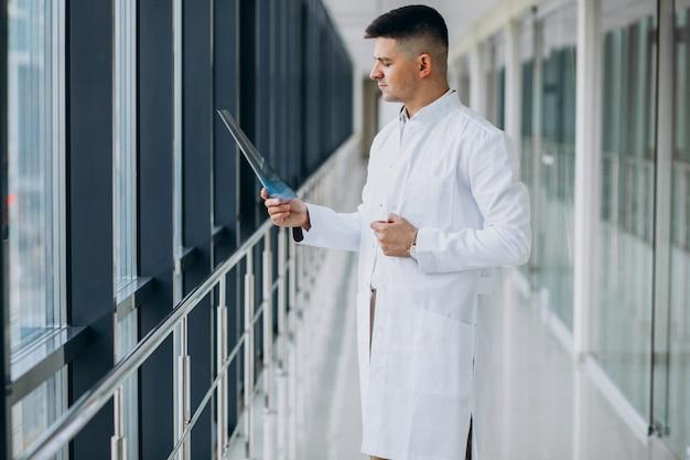 Jovem cirurgião bonito olhando o raio x Foto gratuita