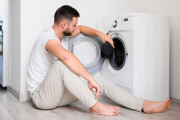 Jovem, colocando as roupas na máquina de lavar Foto gratuita