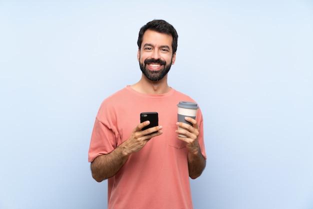 Jovem, com barba, segurando um café para viagem sobre parede azul isolada, enviando uma mensagem com o celular Foto Premium