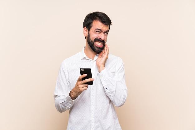 Jovem com barba segurando um celular com dor de dente Foto Premium