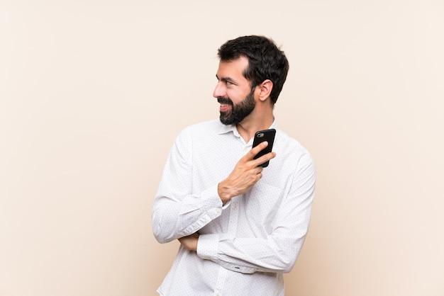 Jovem com barba segurando um celular olhando para o lado Foto Premium