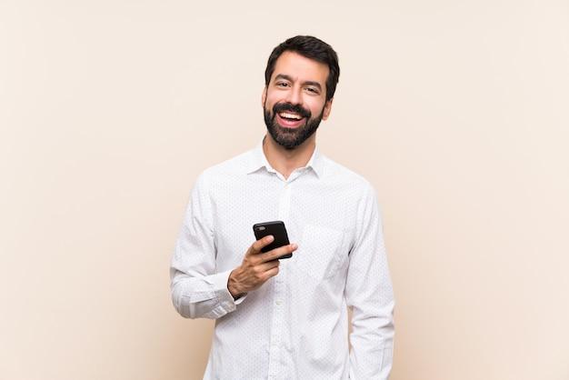 Jovem com barba segurando uma risada móvel Foto Premium