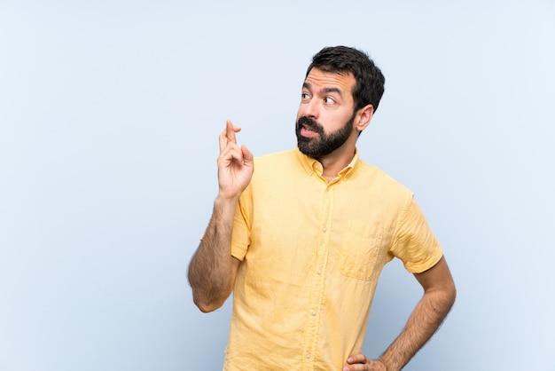 Jovem com barba sobre azul isolado com dedos cruzando e desejando o melhor Foto Premium