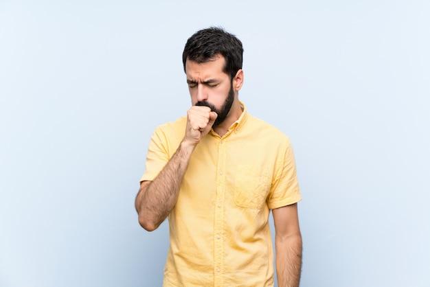 Jovem com barba sobre parede azul isolada está sofrendo de tosse e se sentindo mal Foto Premium