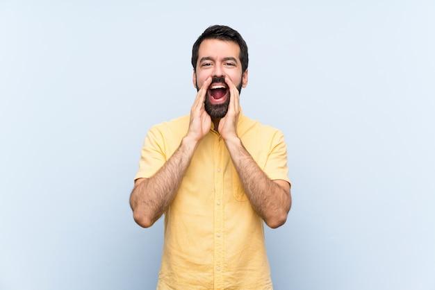 Jovem com barba sobre parede azul isolada, gritando e anunciando algo Foto Premium