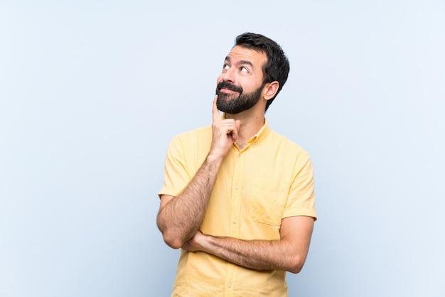 Jovem com barba sobre parede azul isolada, pensando uma idéia enquanto olha para cima Foto Premium