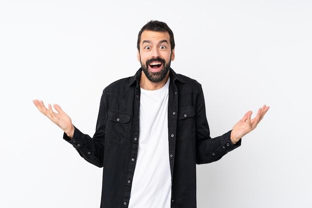 Jovem com barba sobre parede branca isolada com expressão facial chocada Foto Premium