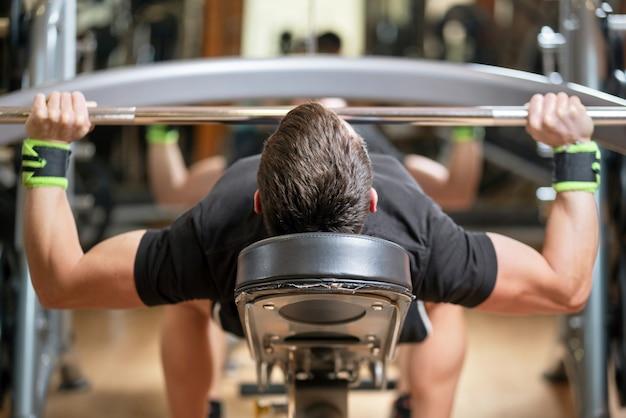 Jovem com barra flexionando os músculos e fazendo supino no ginásio Foto Premium