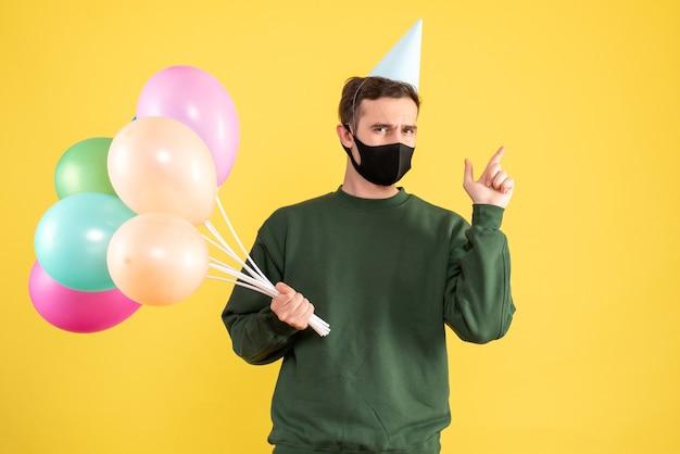 Jovem com boné de festa e balões coloridos apontando para trás em amarelo Foto gratuita