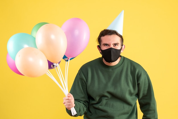 Jovem com boné de festa e balões coloridos em pé sobre amarelo Foto gratuita