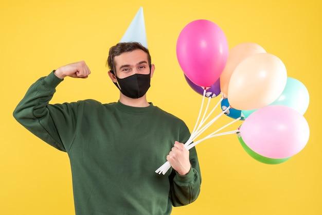 Jovem com boné de festa e balões coloridos mostrando músculo em pé amarelo Foto gratuita