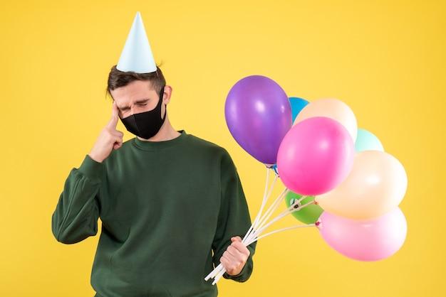 Jovem com boné de festa e balões coloridos segurando a cabeça dele em amarelo. Foto gratuita
