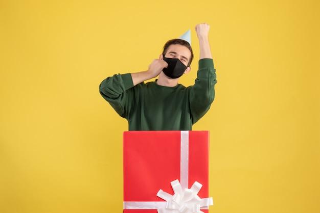 Jovem com boné de festa e máscara preta em frente a uma grande caixa de presente em amarelo Foto gratuita