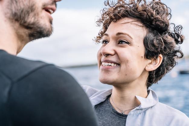 Jovem com cabelo encaracolado e piercing no nariz, olhando para o parceiro com o mar fora de foco no Foto gratuita