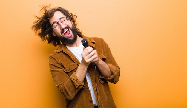 Jovem com cabelo maluco em movimento cantando Foto Premium