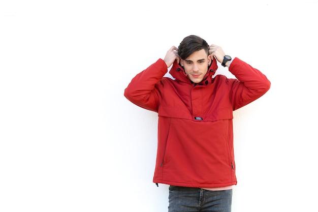 Jovem com casaco vermelho sobre parede branca Foto Premium