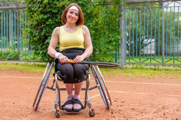 Jovem com deficiência na cadeira de rodas, jogando tênis na quadra de tênis. Foto Premium