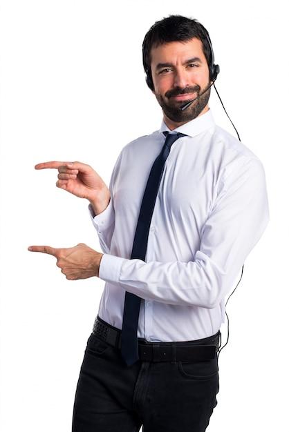 Jovem com fone de ouvido apontando para o lateral Foto gratuita