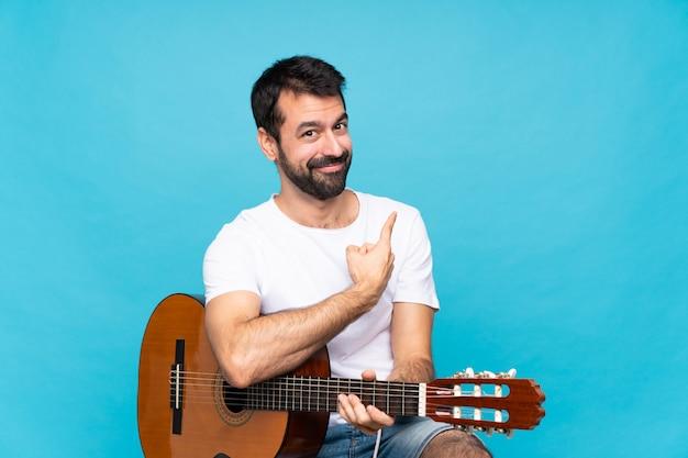Jovem com guitarra sobre azul isolado apontando para trás Foto Premium