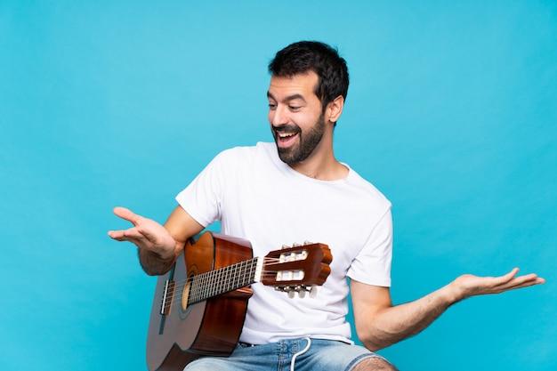 Jovem com guitarra sobre isolado azul segurando copyspace com as duas mãos Foto Premium