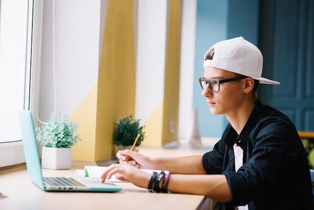 Jovem com laptop na sala de aula Foto gratuita