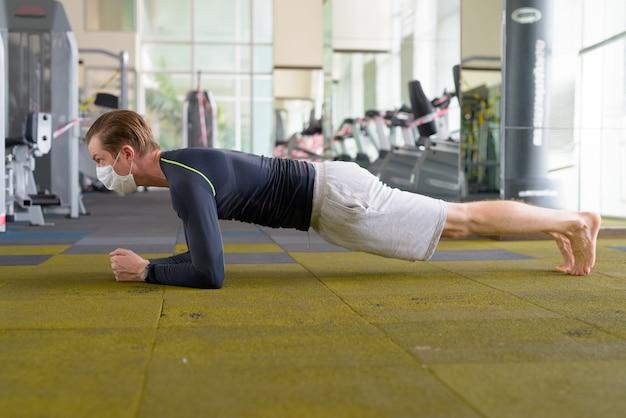 Jovem com máscara fazendo posição de prancha no chão na academia durante coronavírus covid-19 Foto Premium