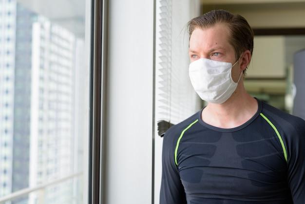 Jovem com máscara para proteção contra surto de coronavírus pensando em se exercitar durante a covid-19 Foto Premium