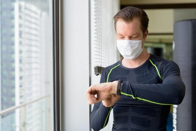 Jovem com máscara para proteção contra surto de coronavírus, verificando smartwatch e pronto para se exercitar durante covid-19 Foto Premium