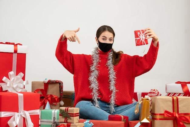 Jovem com máscara preta segurando um presente apontando para ela mesma sentada em volta de presentes em branco Foto gratuita