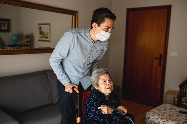 Jovem com máscara protetora, empurrando a cadeira de rodas com uma mulher idosa e doente. família, conceito de atendimento domiciliar. Foto Premium