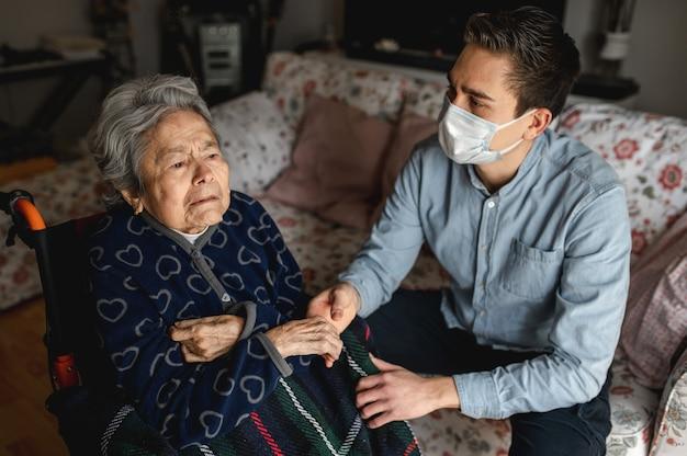Jovem com máscara protetora, sentado ao lado de uma mulher idosa e doente em cadeira de rodas. família, conceito de atendimento domiciliar. Foto Premium