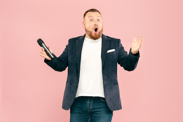 Jovem com microfone em fundo rosa, levando com microfone Foto gratuita