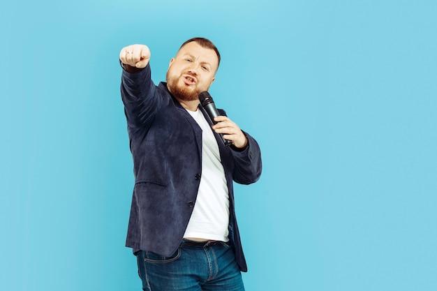 Jovem com microfone na parede azul, conceito principal Foto gratuita