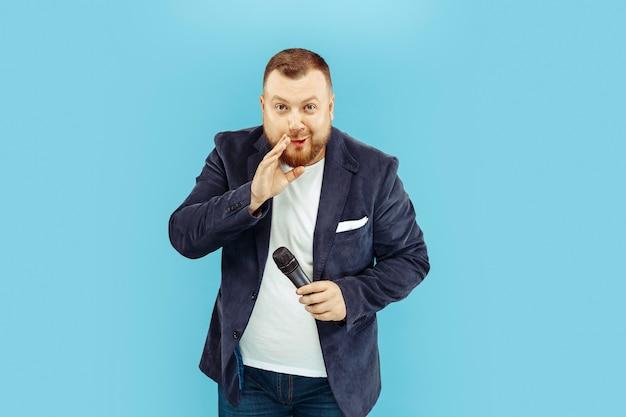 Jovem com microfone na parede azul Foto gratuita