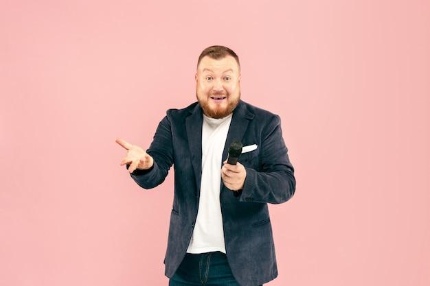 Jovem com microfone na parede rosa Foto gratuita