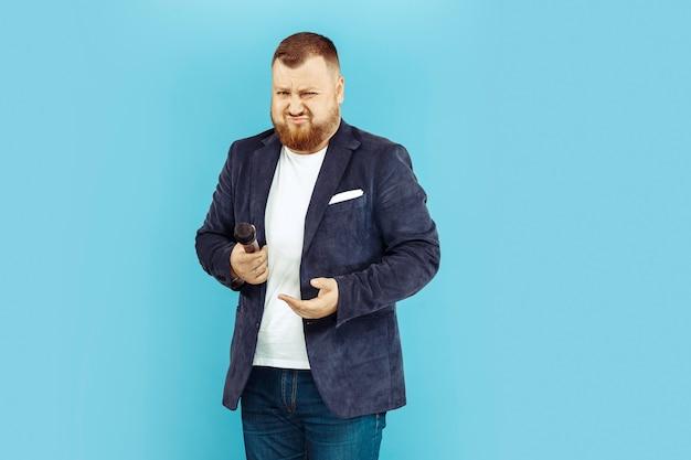 Jovem com microfone no espaço azul, conceito líder Foto gratuita