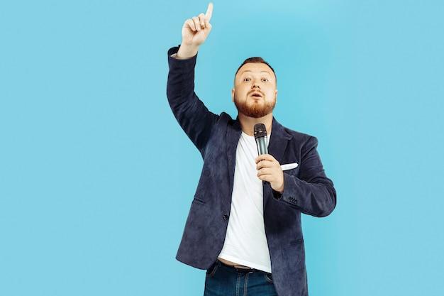 Jovem com microfone no estúdio azul, conceito principal Foto gratuita