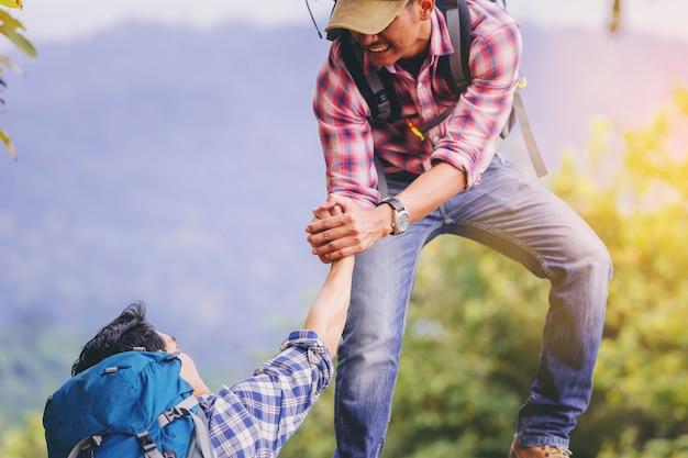 Jovem com mochila ajudando amigo a subir ao topo da montanha. Foto Premium