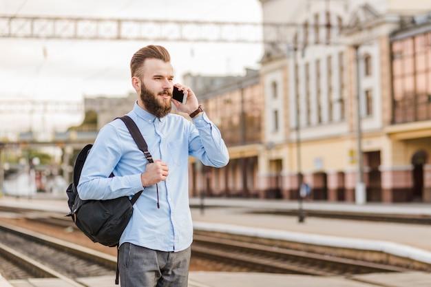 Jovem com mochila falando no celular na estação ferroviária Foto gratuita