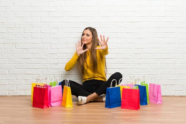 Jovem com muitas sacolas de compras está um pouco nervosa e assustada, esticando as mãos para a frente Foto Premium