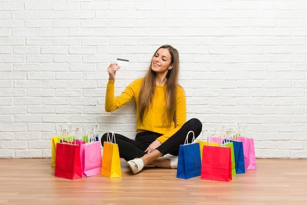 Jovem com muitos sacos de compras, segurando um cartão de crédito e pensando Foto Premium