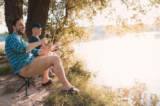 Jovem com o filho e pai pescando no rio. Foto Premium