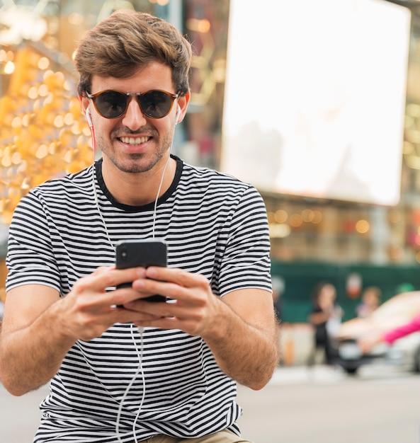 Jovem com óculos de sol digitando smartphone Foto gratuita