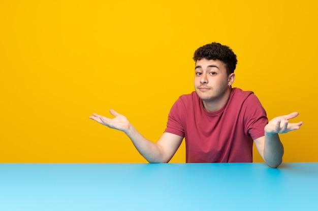 Jovem com parede colorida e mesa com dúvidas ao levantar as mãos Foto Premium