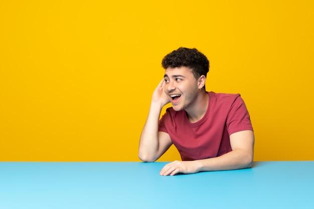 Jovem com parede colorida e mesa ouvindo algo, colocando a mão na orelha Foto Premium