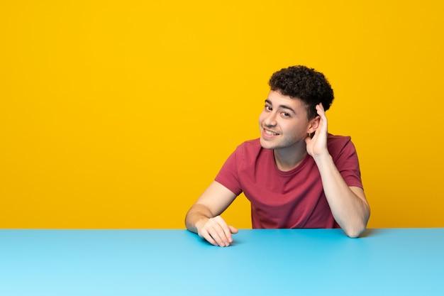 Jovem com parede colorida e mesa ouvindo algo, colocando a mão sobre a orelha Foto Premium