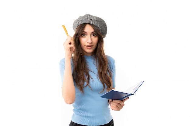 Jovem com sorriso encantador, cabelo castanho longo ondulado, maquiagem linda, em jersey azul, jeans preto, boina cinza, em pé com caneta e caderno Foto Premium