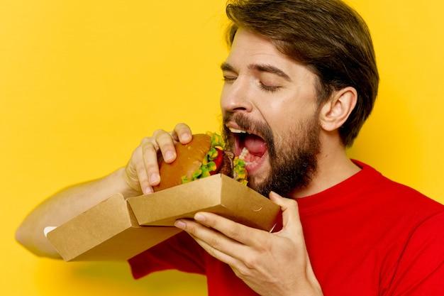 Jovem com um hambúrguer suculento nas mãos, um homem comendo um hambúrguer Foto Premium