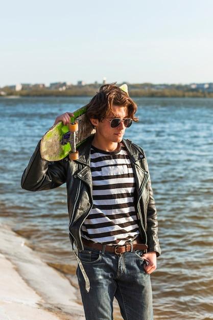 Jovem com um skate perto do mar Foto gratuita